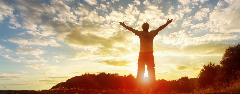 Photo of man looking at sunrise with arms raised