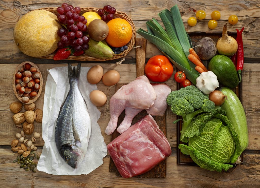 Selection of paleo diet foods on a wooden platter