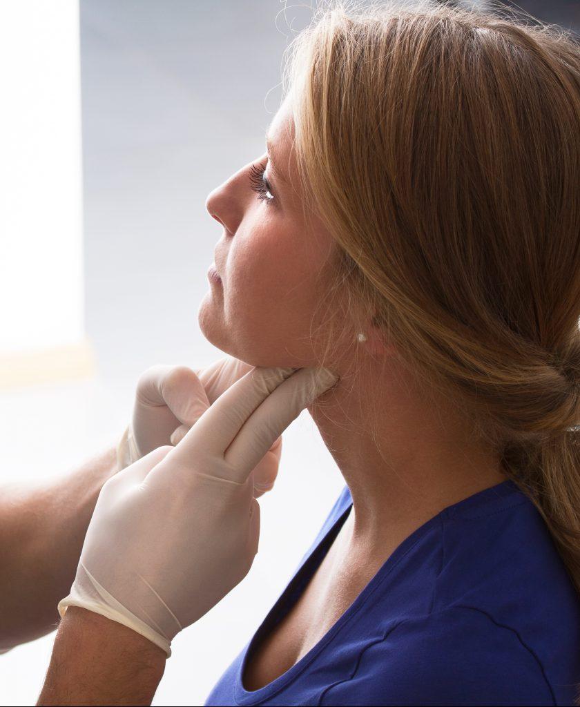 Clinician examining woman's thyroid gland