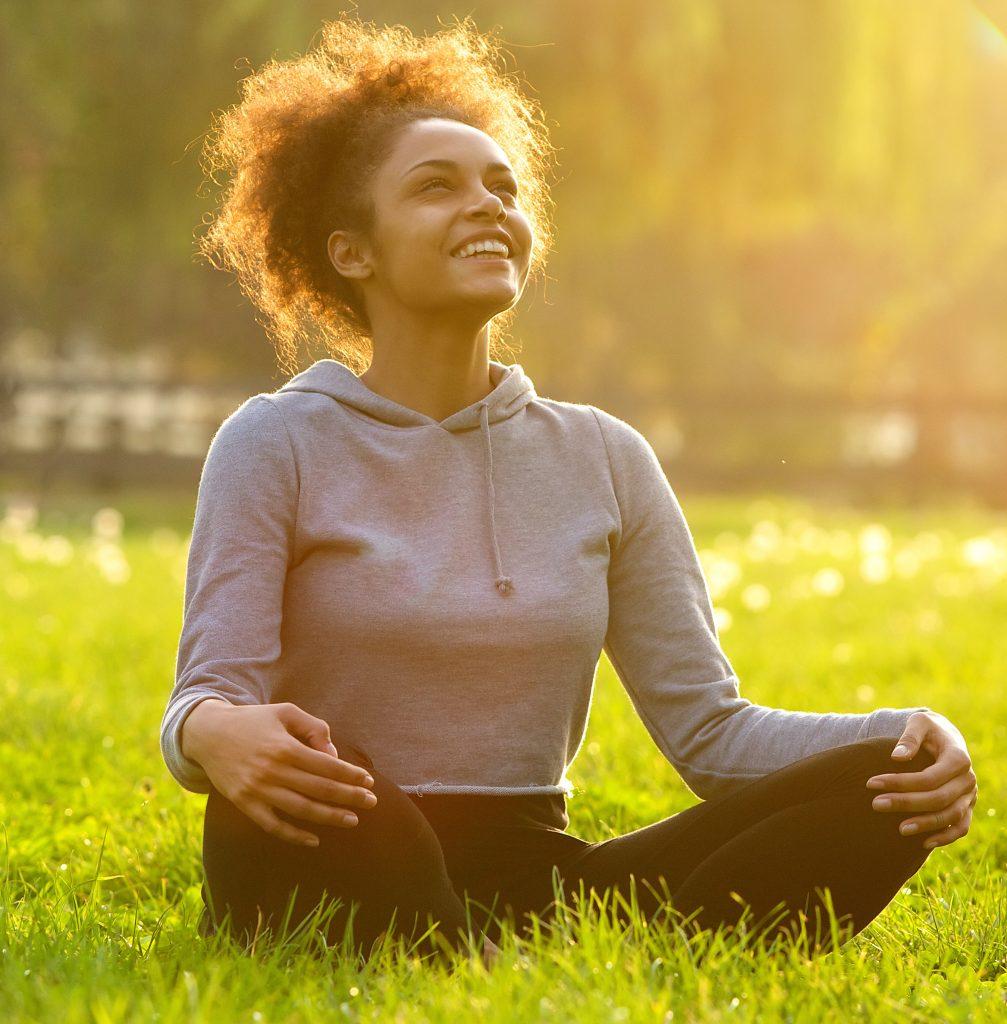 Happy women sitting in a field meditating