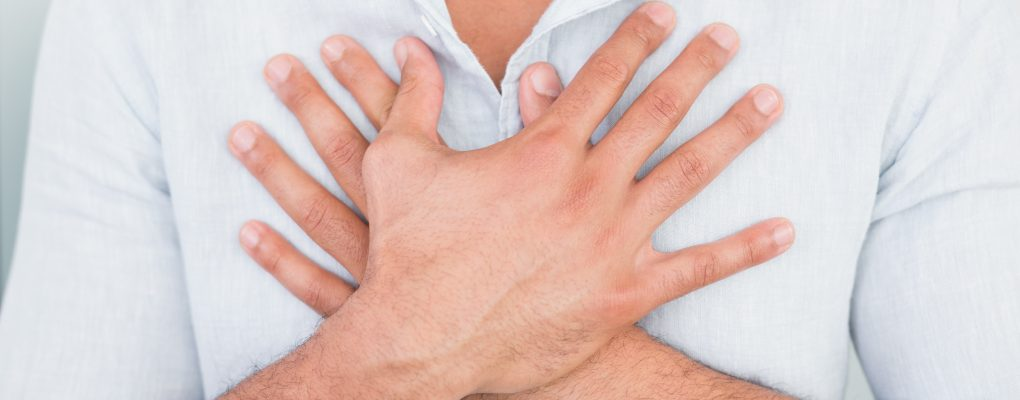 photo of man with heartburn holding chest